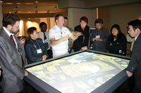Caption: ESRI's Chris LeSueur demonstrates a TouchTable to workshop guests.